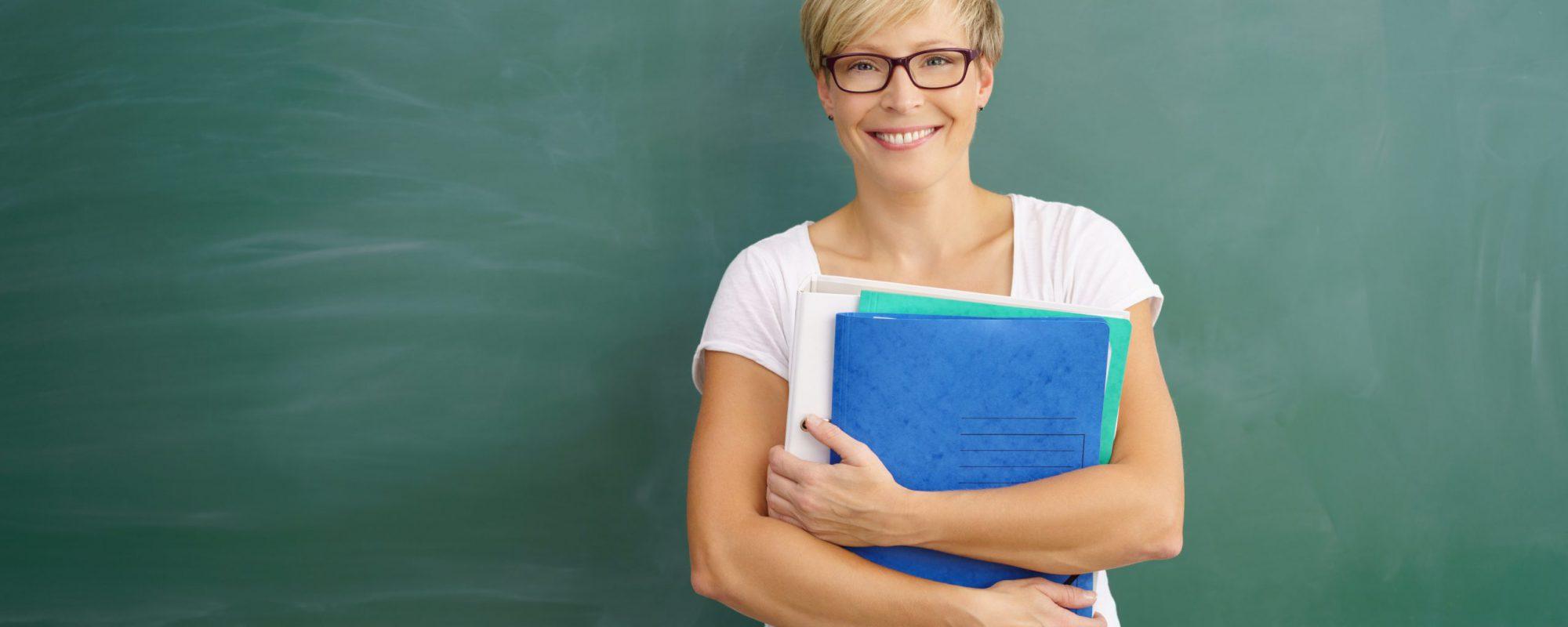 lächelnde lehrerin steht vor einer leeren tafel